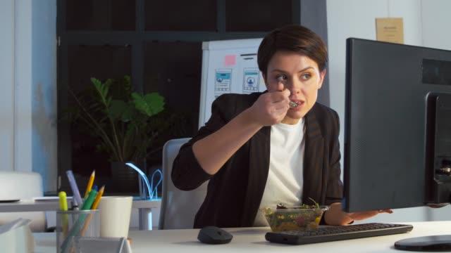 affärs kvinna med dator ätande på nattens kontor video