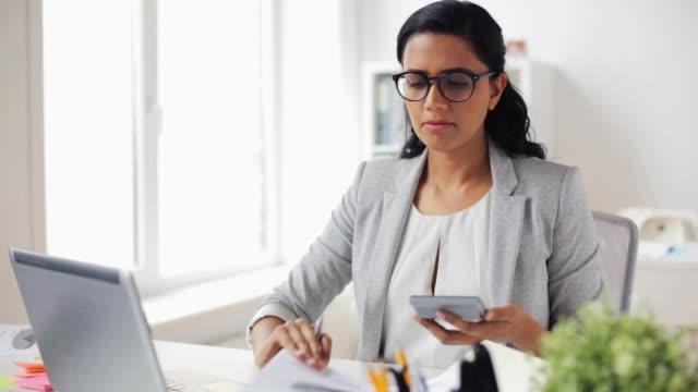 affärskvinna med bärbar dator och kalkylator på kontor video