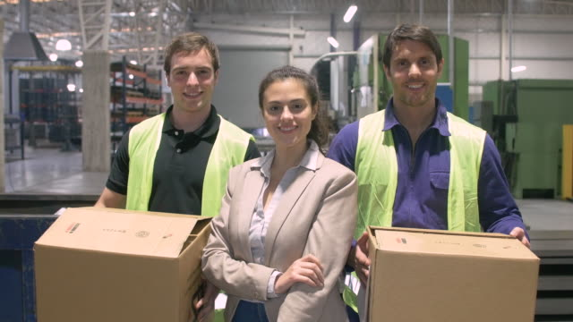 Businesswoman with manual workers carrying boxes video