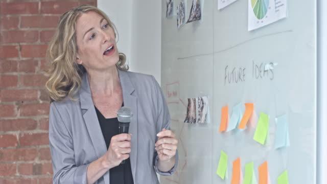 vídeos de stock e filmes b-roll de businesswoman with microphone speaking about the new marketing - orador público