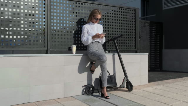 businesswoman with mobile and her scooter next - monopattino elettrico video stock e b–roll