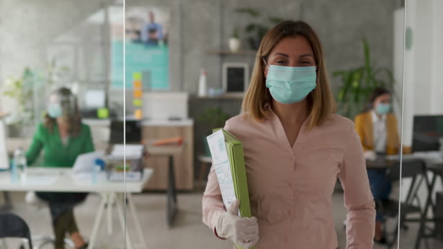 Businesswoman with protective face mask in office Portrait of female bank manager with protective face mask in office, standing, looking at camera and smiling during covid-19 pandemic place of work stock videos & royalty-free footage