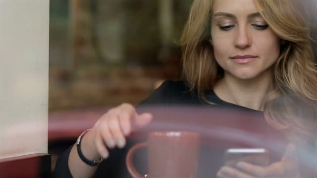Businesswoman with smartphone drinking coffee in cafe video