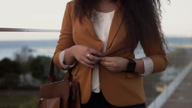 affärskvinna med smartwatch buttoning blazer och gör dig redo för arbete - blazer bildbanksvideor och videomaterial från bakom kulisserna