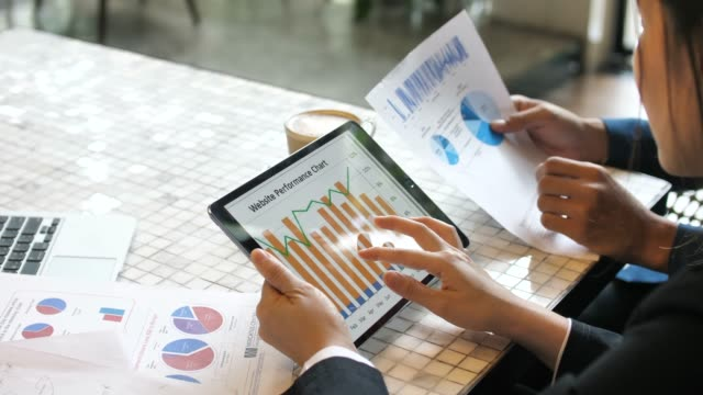 Businesswoman with team analyzing market data on Tablet PC