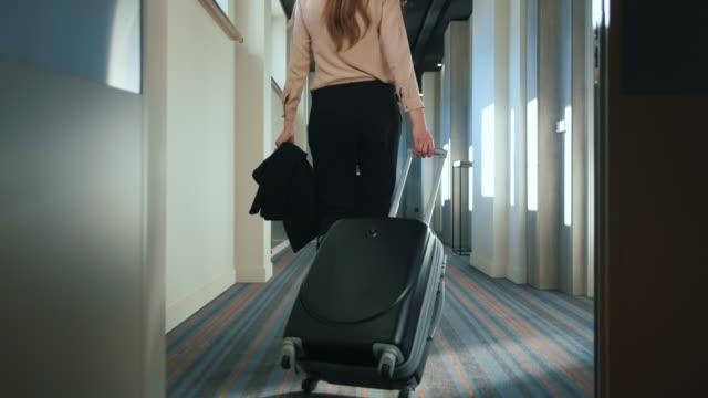 businesswoman with travel suitcase walking at hotel corridor - fare una prenotazione video stock e b–roll