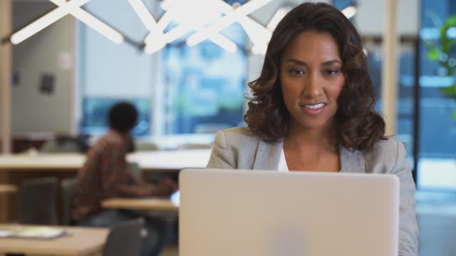 ラップトップ付きの現代オフィスのオフィススペースでデスクで働くビジネスウーマン - 上半身点の映像素材/bロール