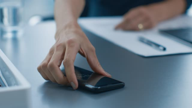Businesswoman Working at Her Office Desk Reaches for Her Smartphone and Starts Typing Important Business Related Email. Woman Picks up Mobile Phone from Her Desk. Focus on a Phone