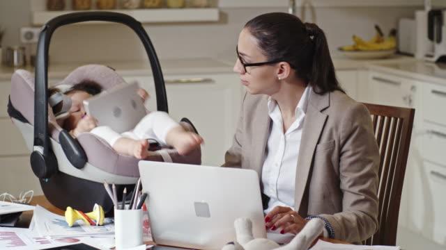Femme d'affaires travaillant de la maison avec bébé à proximité - Vidéo