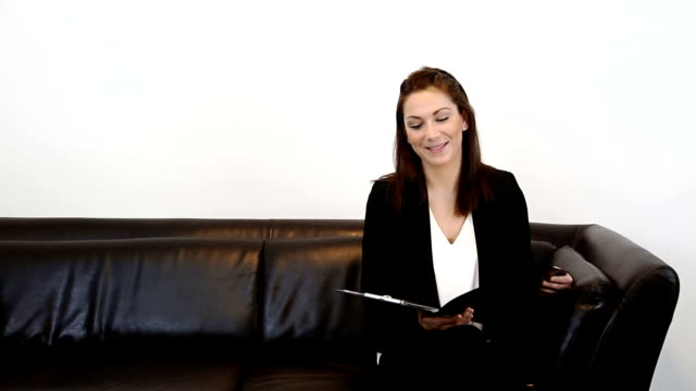 Businesswoman working holding a clipboard A young businesswoman sitting down in a sofa wearing a black jacket and white shirt, holding a clipboard. White background. saleswoman stock videos & royalty-free footage