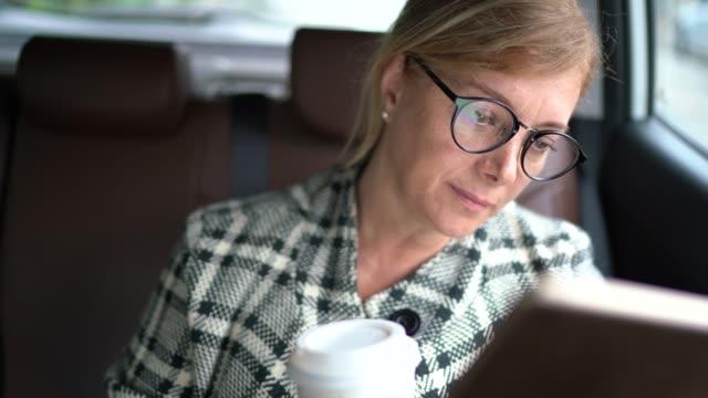 stockvideo's en b-roll-footage met zakenvrouw die in een cabine werkt, met behulp van digitale tablet en koffie drinken - onderweg
