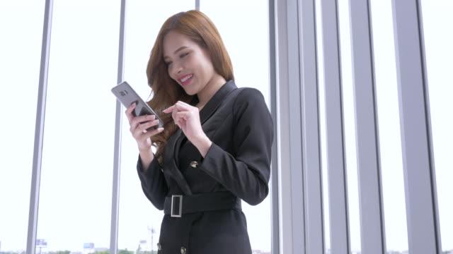 vídeos de stock, filmes e b-roll de mulher de negócios trabalhando em telefone inteligente. jovem empresária asiática, usando telefone - foco difuso