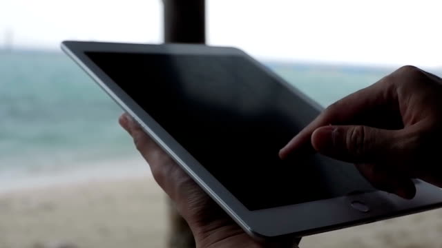 Businesswoman working on tablet computer on the beach.Girl working with tablet PC on beach. video