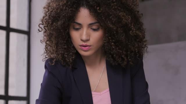 Empresaria trabajando sentado en la oficina - vídeo