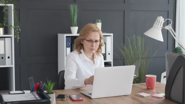 Businesswoman working with filed document and laptop video