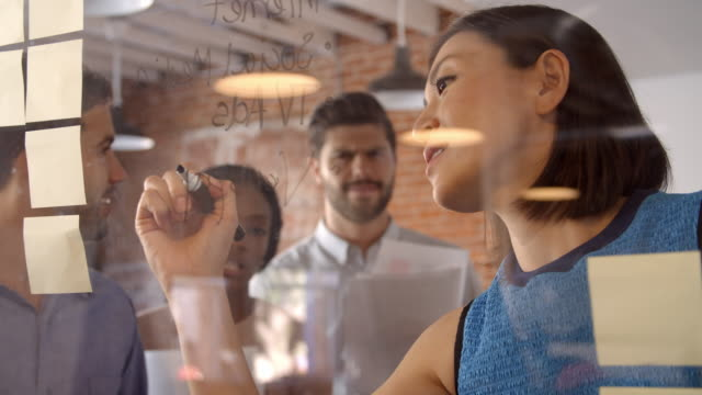 Businesswoman Writing Ideas On Glass Screen During Meeting video