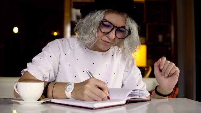 affärskvinna som skriver i den dagliga planner - anteckningsblock bildbanksvideor och videomaterial från bakom kulisserna