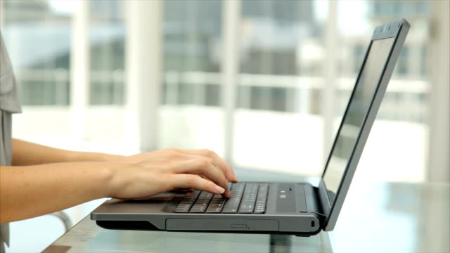 Businesswoman's hands typing on laptop in office video