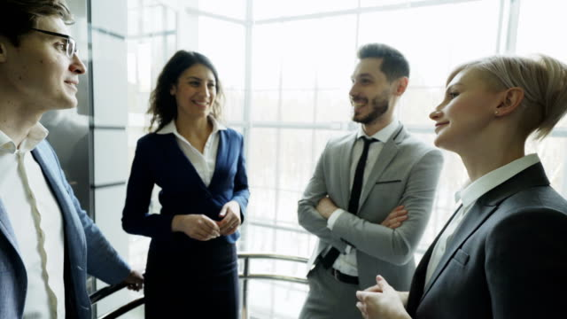 businesswomen and businessmen colleagues talking in moving elevator and come out from it in modern business center - ascensore video stock e b–roll