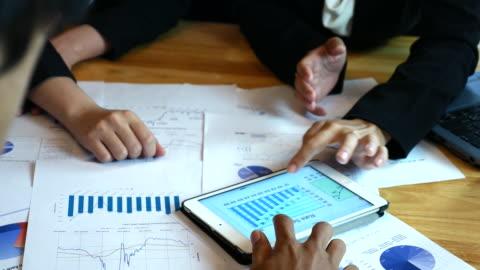 vidéos et rushes de femmes d'affaires et hommes d'affaires agit d'analyse financières avec tablette et imprimés graphiques - client