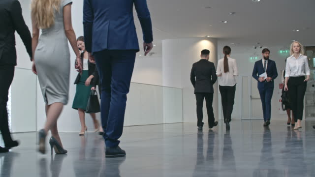 Businesswomen and Businessmen Walking through Hall Ground level shot with PAN of businesspeople in official clothes walking through hall of modern business center and discussing work lobby stock videos & royalty-free footage