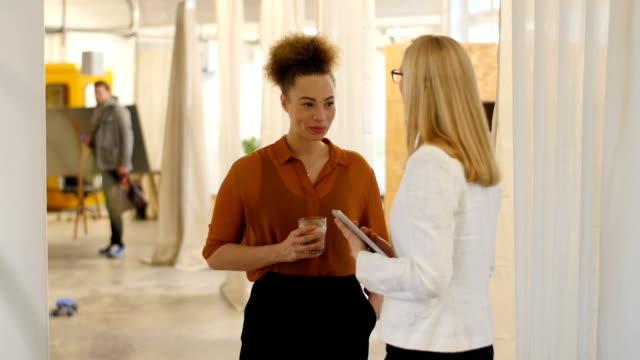 Mujeres de negocio comunicar en oficina creativa - vídeo