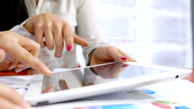 businesswomen discussing on financial data using a tablet computer