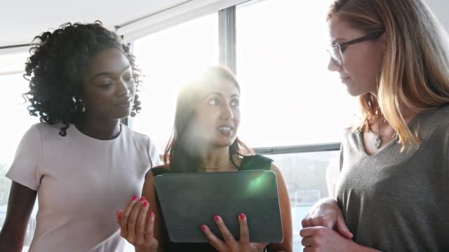 affärskvinnor diskutera över tablet pc i office - ljus belysning bildbanksvideor och videomaterial från bakom kulisserna