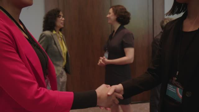 Businesswomen doing handshake in conference