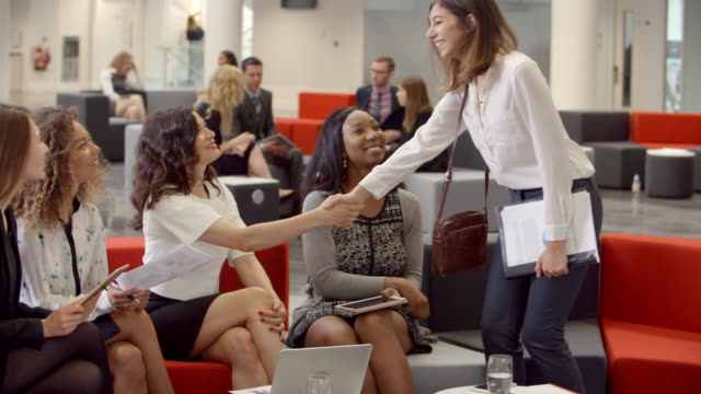 Businesswomen Meeting In Busy Lobby Of Modern Office Businesswomen Meeting In Busy Lobby Of Modern Office conference event stock videos & royalty-free footage