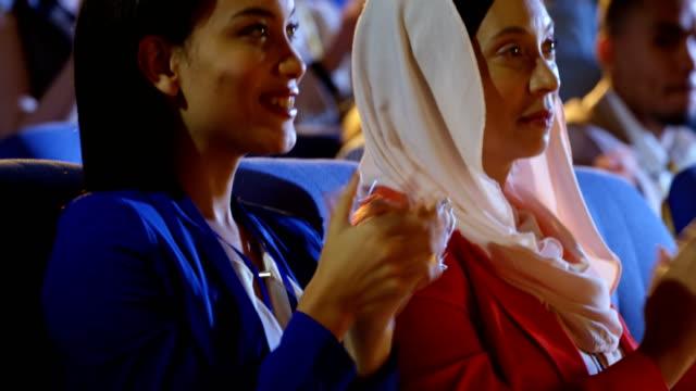 geschäftsfrauen sitzen auf dem sitz und applaudieren im auditorium 4k - zuschauerraum stock-videos und b-roll-filmmaterial