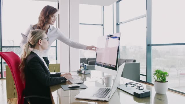businesswomen talking at computer in office, real time - soft focus video stock e b–roll