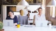 istock Businesswomen using laptops at desk in new office 880341574