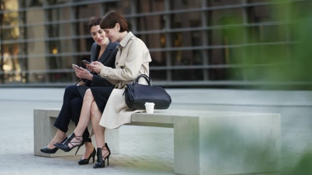 businesswomen using mobile phones on bench in city - collega d'ufficio video stock e b–roll