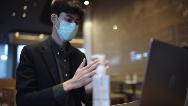 コーヒーショップでラップトップを使用する前に手指消毒剤を使用して忙しい男 - 飲食店点の映像素材/bロール