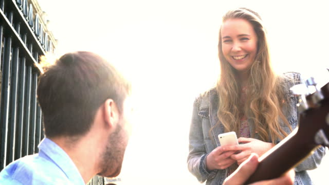 Busker and happy young woman. video