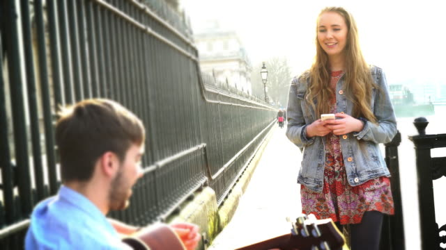 Busker and pretty young woman with phone. video