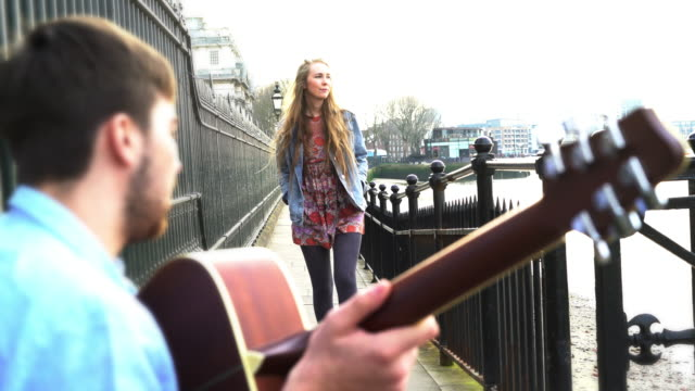 Busker playing guitar and pretty young woman. video