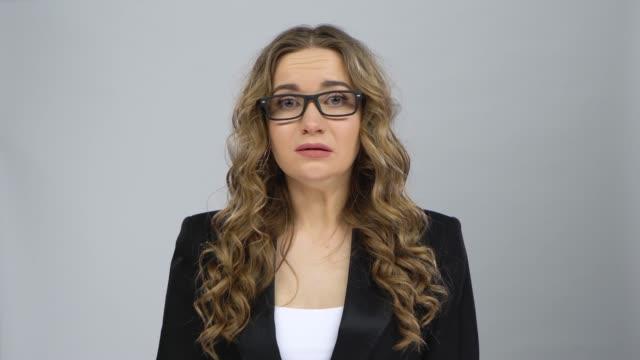 bussines kvinnliga står oroande i förväntan och sedan ler med lättnad på grå bakgrund - blazer bildbanksvideor och videomaterial från bakom kulisserna