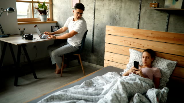 Bussy mornings before work Beautiful, happy, young couple in morning routine, using technology. Man surfing the net on laptop, woman using smart phone while lying in bed shopping online stock videos & royalty-free footage