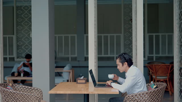 Busy Asian business guy typing on laptop and drink coffee near swimming pool in cafe.