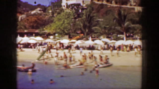 1952: busy beach recreation area blue waters summer tropical fun. - guerrero video stock e b–roll