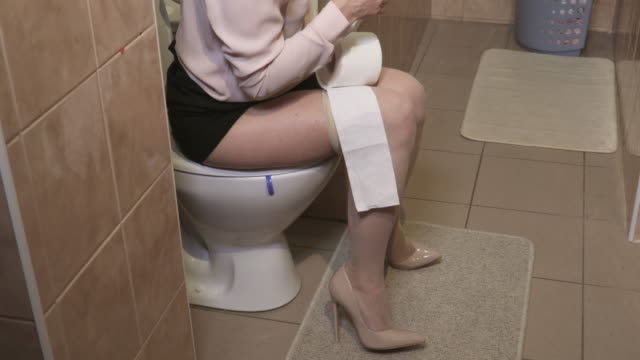 Busy business woman in the toilet using smartphone - vídeo