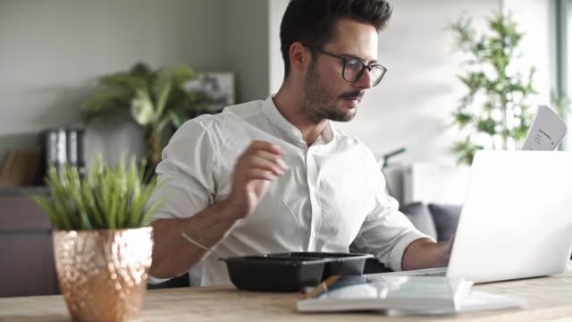 uomo d'affari impegnato a mangiare in ufficio - pranzo video stock e b–roll