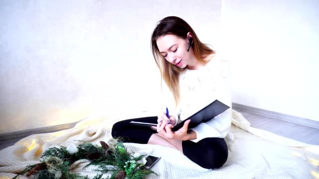 evde çalışan ve ekose garland ile parlak oda katta oturan kulaklıktaki iletişim karar verme meşgul iş kadını - bluetooth stok videoları ve detay görüntü çekimi