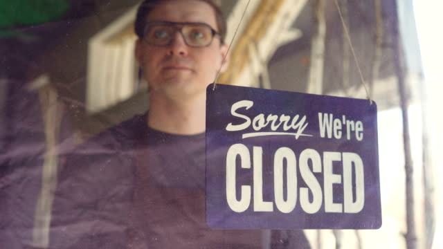 """vídeos y material grabado en eventos de stock de camarero de cafetería ocupado en delantal es mirar fuera a través de puerta de cristal y cambiar placa de puerta de """"lo sentimos estamos cerrados"""" a """"sí estamos abiertos"""". a partir de día de trabajo y concepto de negocio. - abierto"""