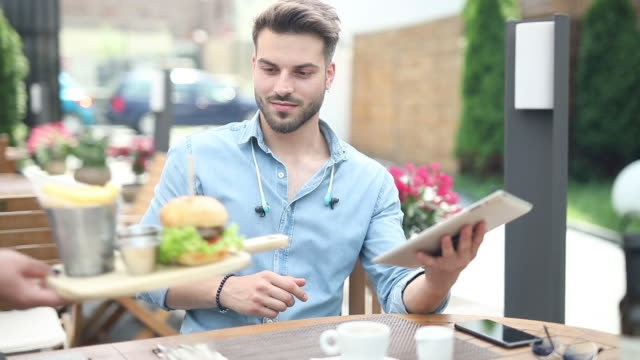 busy casual man works on his tablet while the waiter brings his his order - terrazza video stock e b–roll