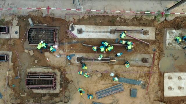 vídeos y material grabado en eventos de stock de sitio de trabajo de construcción ocupado, vista aérea, muchos hombres, trabajador es el trabajo en el sitio civil - material de construcción