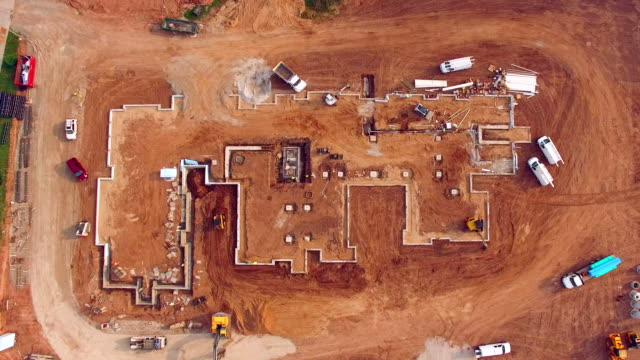 Busy construction job site, aerial view, many men working