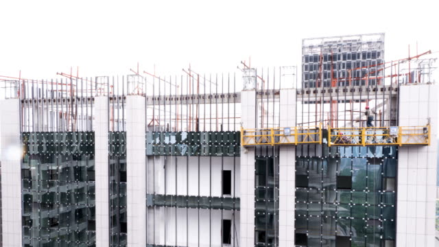 Busy construction workers installing building glass wall, time lapse. video